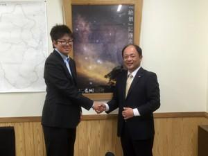 表敬訪問した熊谷秀樹村長と握手する学生